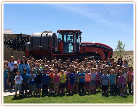 Students pose for a photo in front of a sprayer display at the SAGE Center
